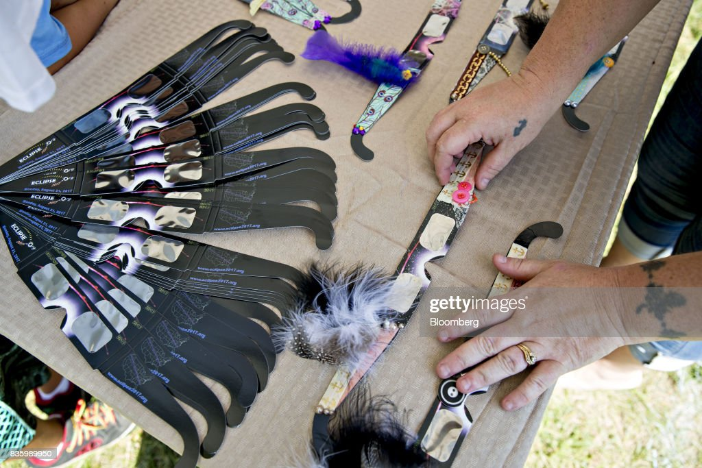 A vendor arranges decorated solar viewing glasses during an arts and crafts fair ahead of a total solar eclipse on the campus of Southern Illinois University (SIU) in Carbondale, Illinois, U.S., on Sunday, Aug. 20, 2017. Millions of Americans across a 70-mile-wide (113-kilometer) corridor from Oregon to South Carolinawill see the sky darken as the sun disappears from view, albeit for only a few minutes at a time. Photographer: Daniel Acker/Bloomberg via Getty Images