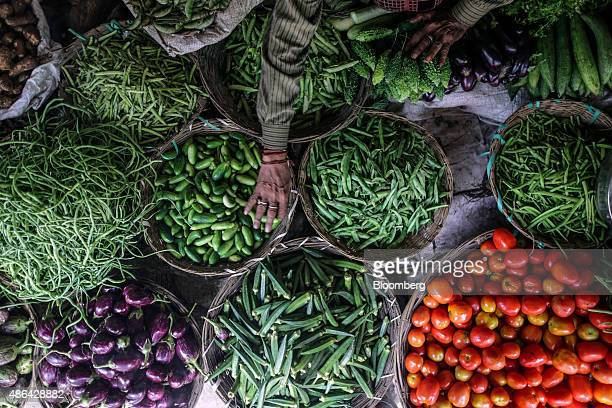 A vendor arranges different types of vegetables at a stall in a vegetable market in Mumbai India on Tuesday Sept 1 2015 Prices of the vegetable a...