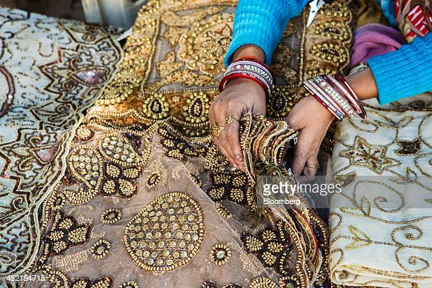 A vendor arranges fabrics at her stall in the Janpath Market in New Delhi India on Tuesday Nov 26 2013 India is scheduled to release thirdquarter...