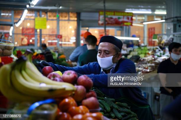 A vendor arranges fruits and vegetables at a market in Almaty on April 25 amid the coronavirus pandemic