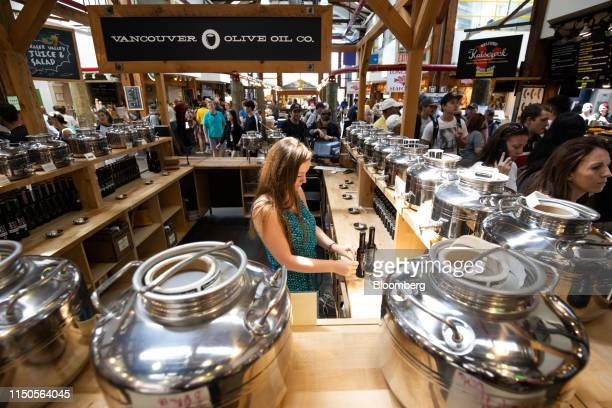 A vendor arranges olive oil bottles at the Granville Island Public Market in Vancouver British Columbia Canada on Sunday June 2 2019 Statistics...