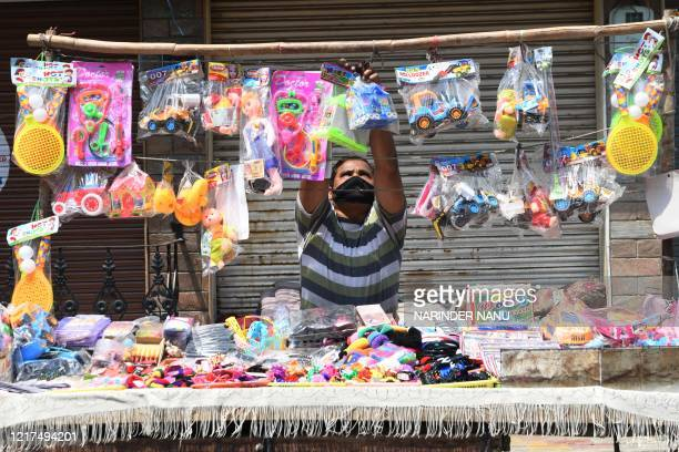 Vendor arranges plastic toys at his stall after the government eased restrictions imposed as a preventive measure against the COVID-19 coronavirus,...