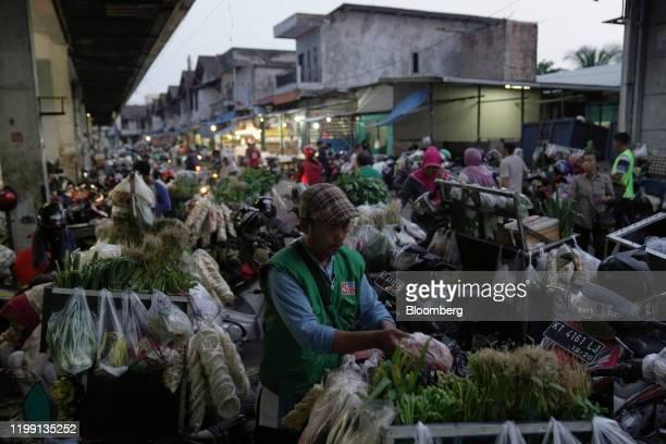 Vendor arranges vegetables at a market in the port city of Balikpapan in East Kalimantan, Borneo, Indonesia, on Tuesday, Nov. 26, 2019. For Jakarta,...