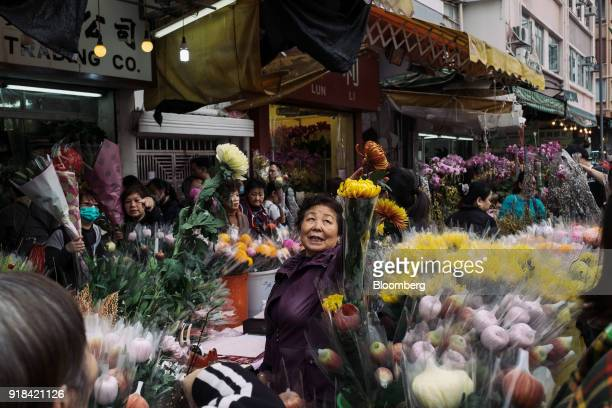 A vendor assists a customer at a flower market ahead of Lunar New Year in the Mong Kok district of Hong Kong China on Wednesday Feb 14 2018 The...