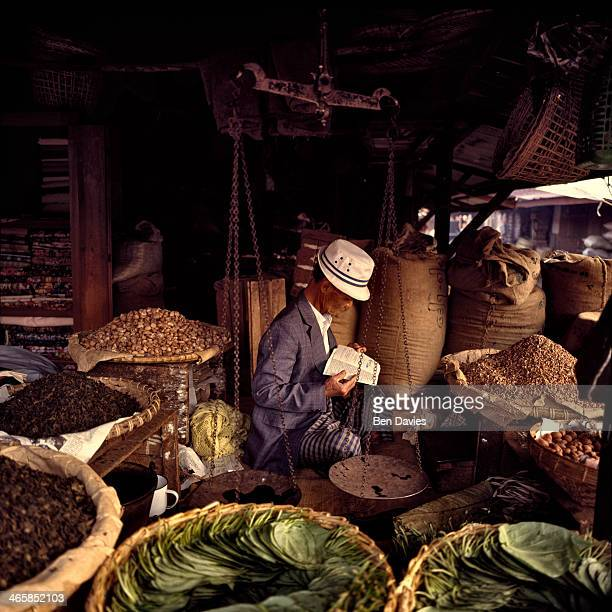 A vendor at a roadside market in Pyin U Lwin formerly known as Maymyo in Myanmar The vendor sells garlic ginger cabbage and many other Burmese spices...