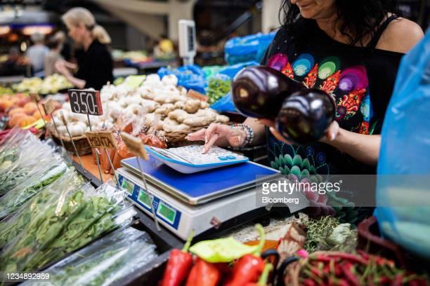 Vendor calculates a price on a fresh produce stall inside Lehel Market in Budapest, Hungary on Thursday, Aug. 26, 2021. Hungarys economy shot higher...