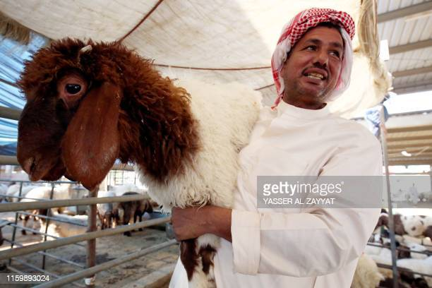 A vendor carries a sheep at a livestock market in Kuwait City on August 5 ahead of the Muslim holiday of Eid alAdha or the Feast of Sacrifice which...