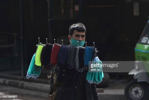 Vendor carries facemasks for sale on a deserted street during a lockdown amid concerns over the spread of the COVID-19 novel coronavirus, in Lahore's...