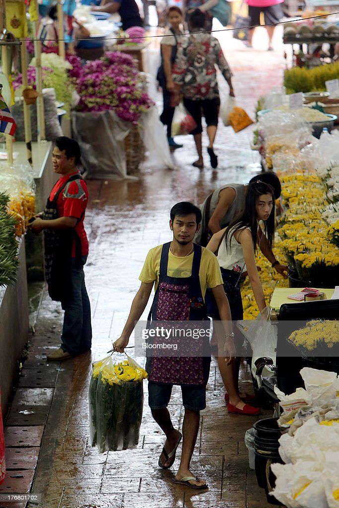 A vendor carries flowers at the Pak Khlong market in Bangkok, Thailand, on Sunday, Aug. 18, 2013. Thai economic growth slowed for a second quarter as exports cooled and local demand weakened, with rising household debt restricting the scope for monetary easing. Photographer: Dario Pignatelli/Bloomberg via Getty Images