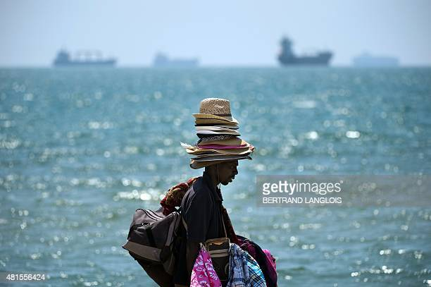 A vendor carries his wares along a beach next to an industrial area in Fossur Mer southern France on July 22 while ozone pollution reached peaks in...