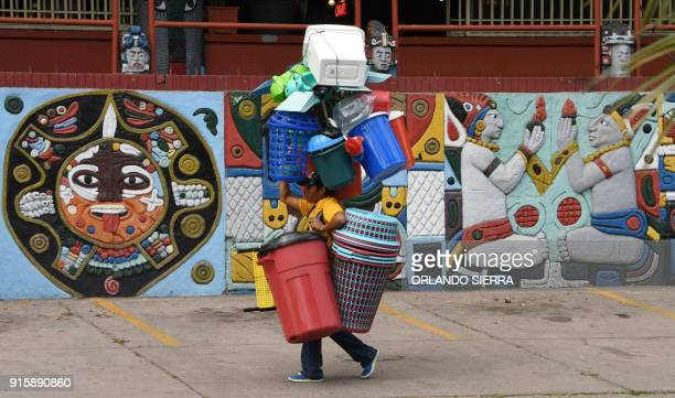 TOPSHOT A vendor carries plastic household items on a central street in Tegucigalpa on February 8 2018 / AFP PHOTO / ORLANDO SIERRA