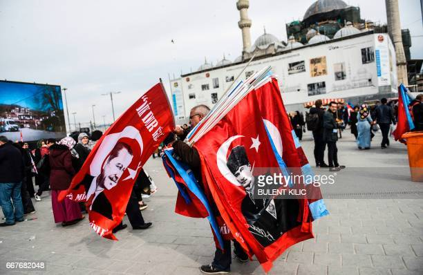 A vendor carries Turkish national flag with a portrait of Turkey's modern founder Mustafa Kemal Ataturk and Turkish president Recep Tayyip Erdogan in...