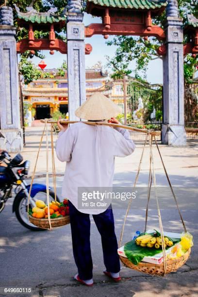 Vendor carrying fruit baskets on city sidewalk