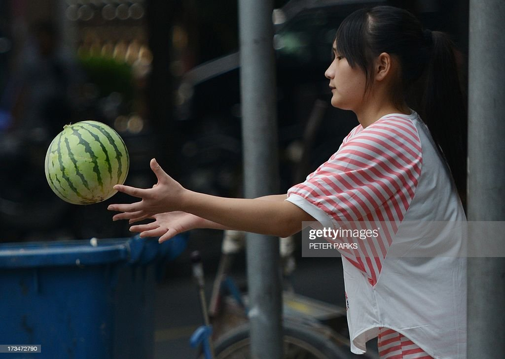 A vendor catches a watermelon outside a market in Shanghai on July 15, 2013. China's gross domestic product expanded 7.5 percent in the April-June quarter, official data showed, a second consecutive slowdown in growth as worries mount over the health of the world's number two economy. AFP PHOTO/Peter PARKS