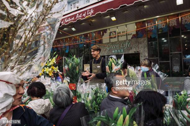 A vendor center calls for customers at a flower market ahead of Lunar New Year in the Mong Kok district of Hong Kong China on Wednesday Feb 14 2018...