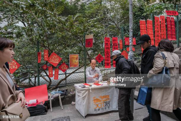 A vendor center writes Chinese calligraphy on decorations at a market stall ahead of Lunar New Year in the Sheung Wan district of Hong Kong China on...