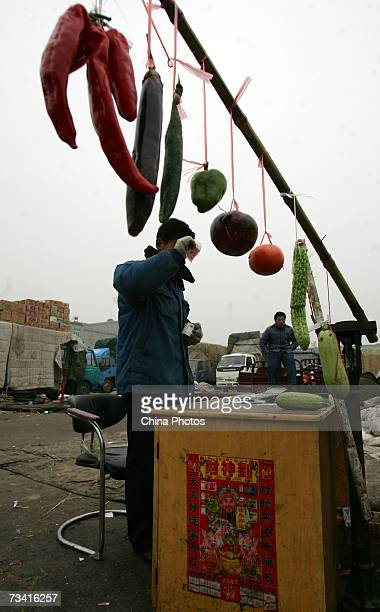 A vendor checks a note at the Xinfadi Vegetable Auction Market on February 25 2007 in Beijing China Xinfadi is the largest of the 4000 vegetable...