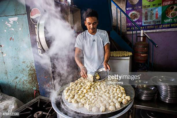 A vendor cooks dumplings at a local market in Kathmandu Nepal on Friday May 29 2015 Nepal's gross domestic product will probably grow 38% in the year...