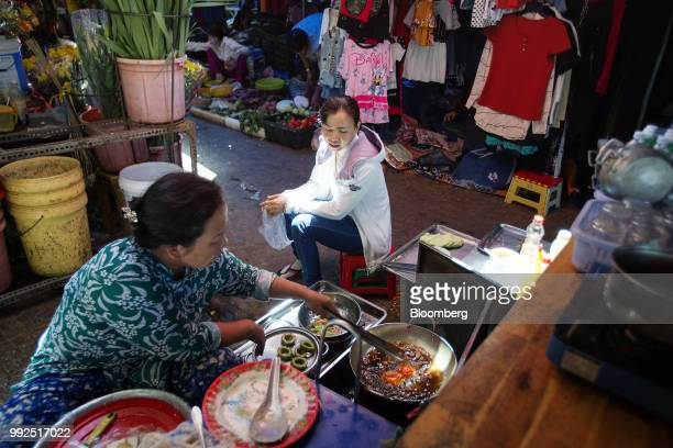 A vendor cooks food as a customer sits waiting at a market stall in Ho Chi Minh City Vietnam on Wednesday June 20 2018 For decades Vietnamese have...