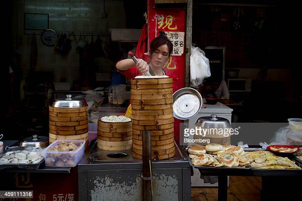 A vendor cooks food in bamboo steamer baskets at a stall in the Gongbei district of Zhuhai Guangdong province China on Sunday Nov 16 2014 Investors...