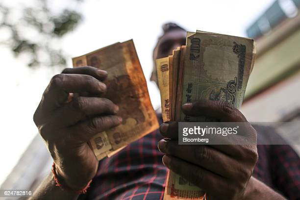 A vendor counts Indian rupee banknotes at a vegetable wholesale market in Mumbai India on Saturday Nov 19 2016 India's top court refused to stay...