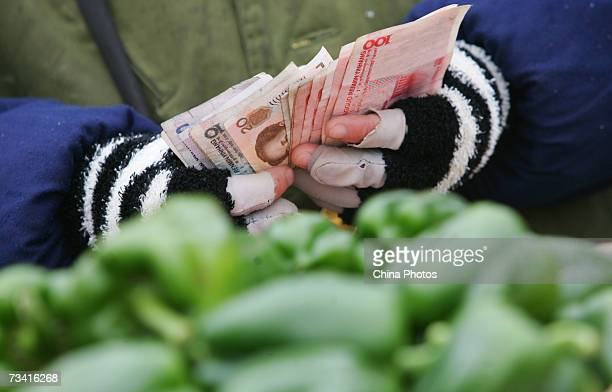 A vendor counts notes at the Xinfadi Vegetable Auction Market on February 25 2007 in Beijing China Xinfadi is the largest of the 4000 vegetable...