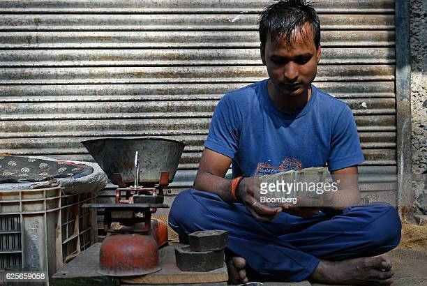 A vendor counts one hundred rupee banknotes at a wholesale market in Delhi India on Friday Nov 25 2016 India's government is grappling with a furor...