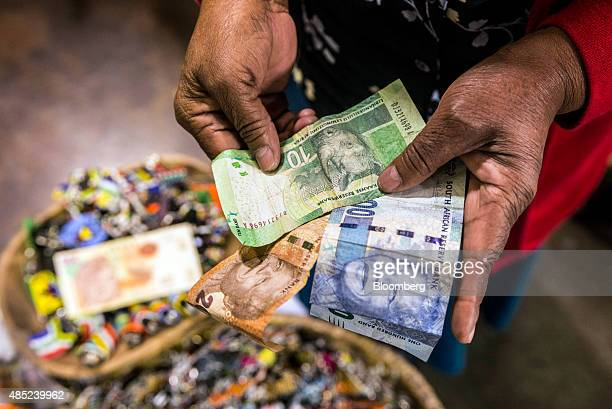 A vendor counts out rand banknotes while working in an African craft market in the Rosebank district of Johannesburg South Africa on Wednesday Aug 26...