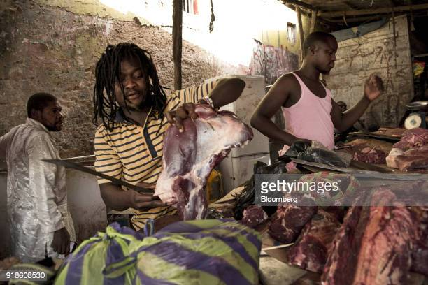 A vendor cuts fresh meat for sale at Bandim market in Bissau GuineaBissau on Tuesday Feb 13 2018 The International Monetary Fund said an increase in...