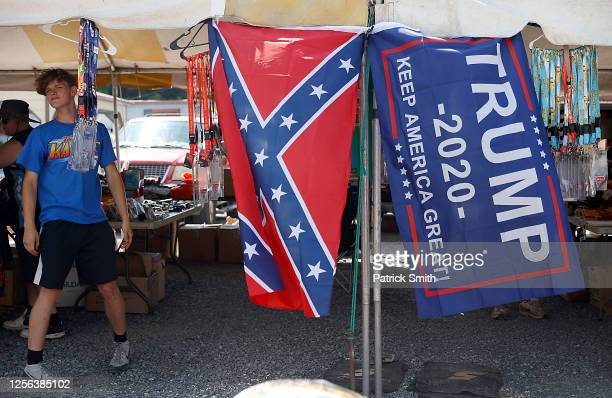 """Vendor displays a confederate and Trump 2020 """"Make America Great Again!"""" flag outside of the Bristol Motor Speedway prior to the NASCAR Cup Series..."""
