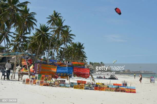 Vendor displays his goods while a tourist flies a kite on the beach near Mombasa, Kenya, on August 11, 2017. Kenya, which held elections on August 8...