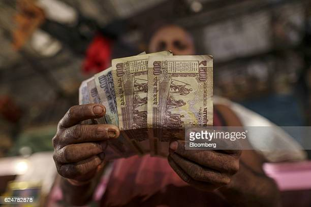 A vendor displays Indian five hundred one hundred and fifty rupee banknotes for photograph at a vegetable wholesale market in Mumbai India on...