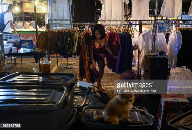 A vendor emerges from the back of her clothing stall at a night market in Bangkok on June 7 2018