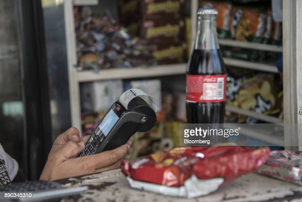 A vendor enters information into a credit card reader for a customer making a purchase at a stand in the Chacao district of Caracas Venezuela on...