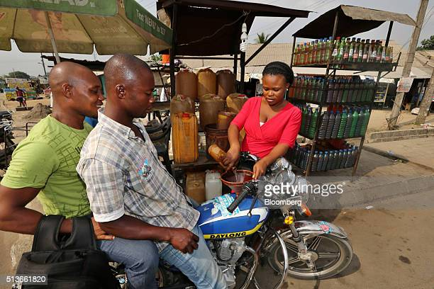 A vendor fills a customer's motorcycle with a bottle of gasoline at a roadside stall in KDare Nigeria on Wednesday Jan 13 2016 Twenty years after the...