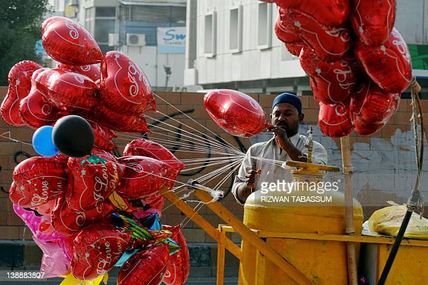 A vendor fills heartshaped balloons with helium gas as he waits for the customers in Karachi on February 13 on the eve of Valentines Day The holiday...