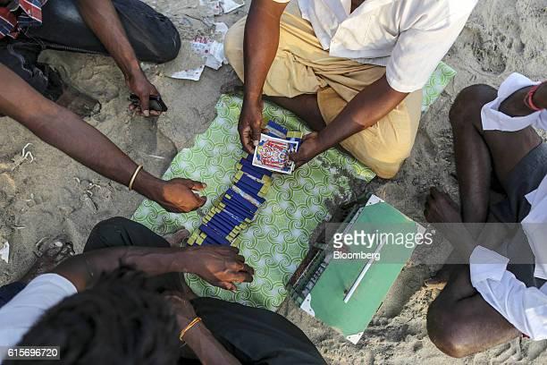 Vendor gives a tarot card reading to visitors at Velankanni Beach in Nagapattinam, Tamil Nadu, India, on Saturday, Oct. 15, 2016. India's new central...