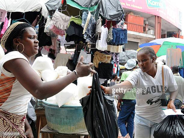 A vendor hands a client her goods in a shopping bag made from nonrecyclable plastic in a market in Libreville on June 29 2010 'It is a revolution in...
