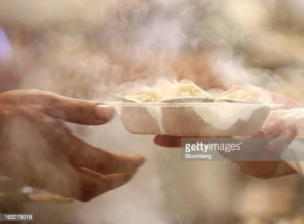 A vendor hands a dish of dumplings to a customer at a stall in a market at night in Beijing China on Wednesday March 6 2013 China maintained its...