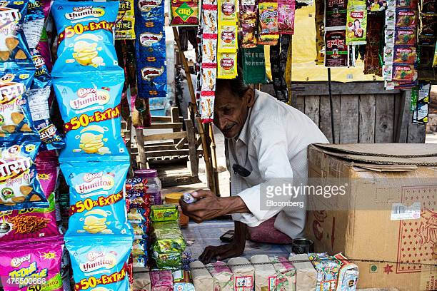 A vendor hands over a pack of bidi cigarettes to a customer unseen at a street stall in Kannauj Uttar Pradesh India on Wednesday June 3 2015 India's...