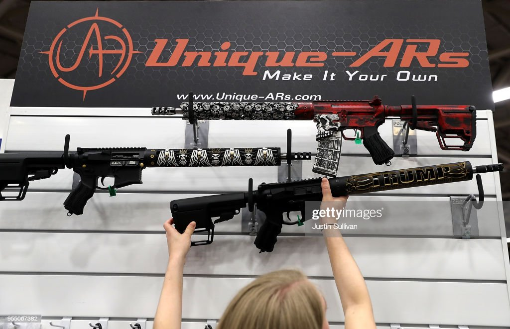 A vendor hangs an AR15 rifle with a custom 'Trump - Make America Great Again' hand guard at the Unique ARs booth during the NRA Annual Meeting & Exhibits at the Kay Bailey Hutchison Convention Center on May 5, 2018 in Dallas, Texas. The National Rifle Association's annual meeting and exhibit runs through Sunday.