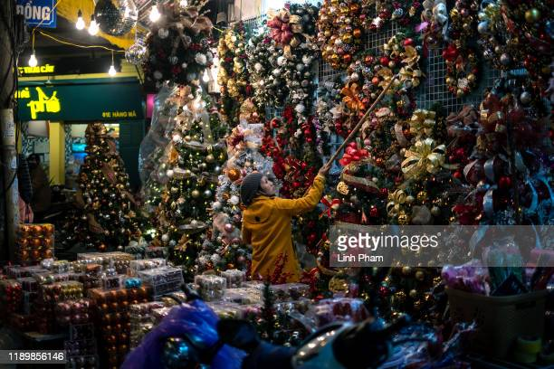 A vendor hangs Christmas decorations at a store on Hang Ma street on December 21 2019 in Hanoi Vietnam As a predominantly Buddhist nation Christmas...