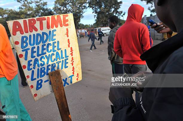 A vendor holding US dollar notes sells phone cards outside a market in Harare on April 14 2010 Zimbabwe marks three decades of independence on April...