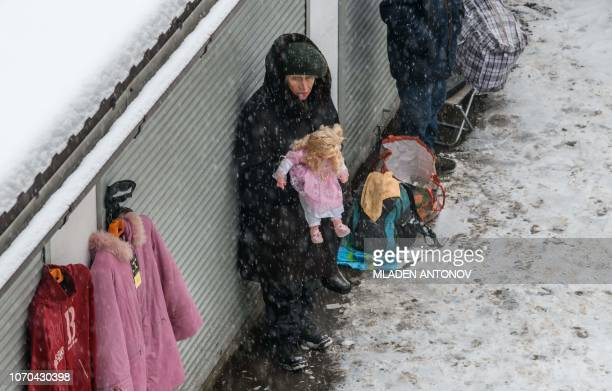 A vendor holds a doll for sale under the snow at Izmailovo flea market in Moscow on December 9 2018