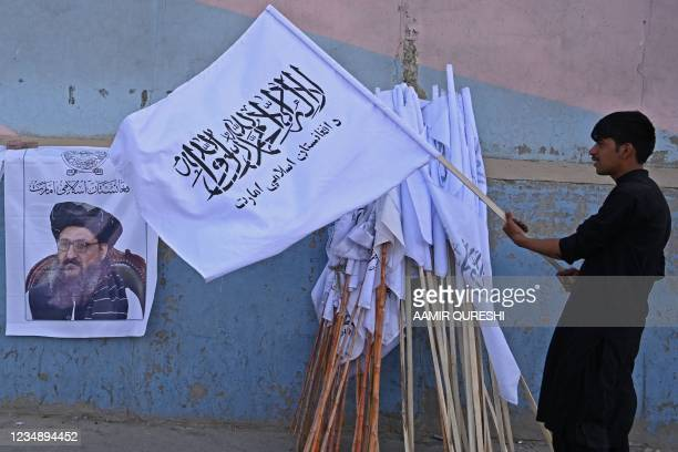 Vendor holds a Taliban flag next to a poster of Taliban leader Abdul Ghani Baradar as he waits for customers along a street in Kabul on August 27,...