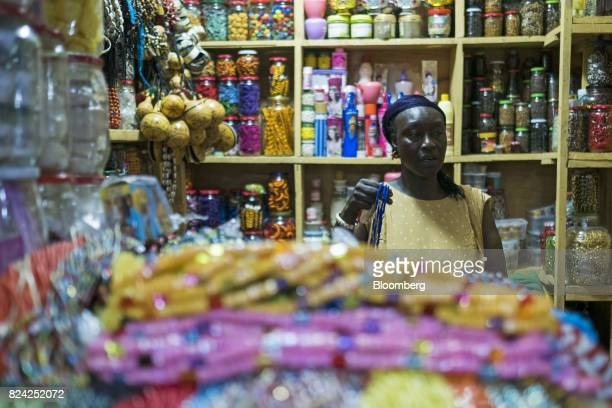 A vendor holds jewelry at a stall in the Malian market in the Plateau district of Dakar Senegal on Friday July 28 2017 Senegalese voters will elect a...