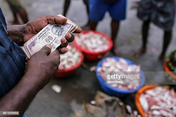 A vendor holds mixed denominations of India rupee banknotes while standing near baskets of fish at the Kasimedu fish market at the Royapurum fishing...
