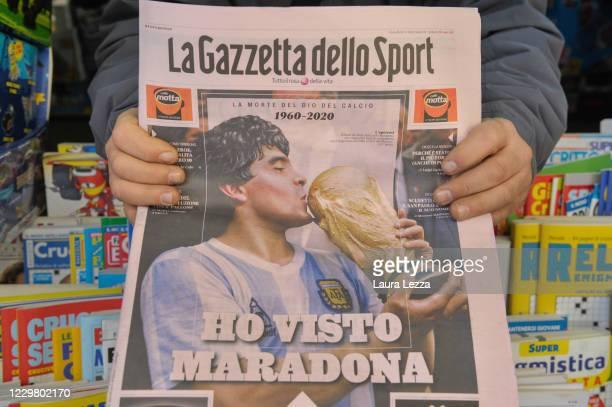 Vendor holds up a copy of Italian sports newspaper La Gazzetta dello Sport which shows a photo of the footballer Diego Armando Maradona on its front...