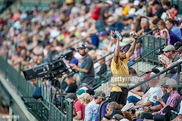 A vendor holds up beer soda and water during a regular season Major League Baseball game between the Atlanta Braves and the Colorado Rockies at Coors...