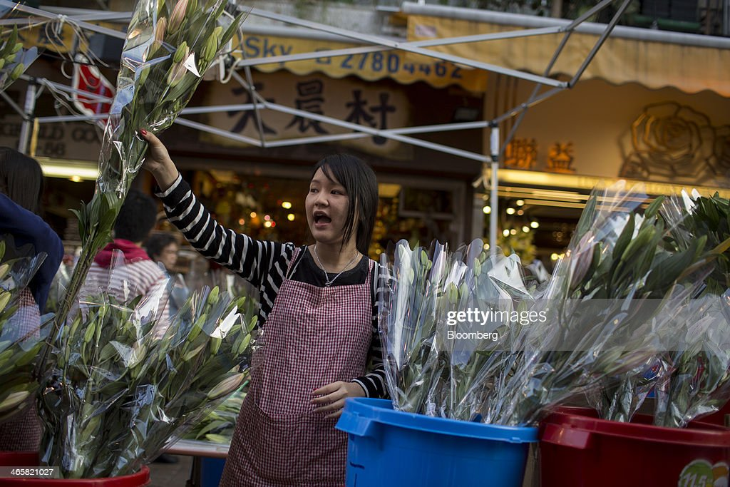 A vendor holds up lilies for sale for the Lunar New Year at a flower market in the Mongkok district of Hong Kong, China, on Wednesday, Jan. 29, 2014. The citys financial markets will close early on Jan. 30 for the Chinese New Year holidays and resume trading on Feb. 4, while those in the mainland will be shut from tomorrow through Feb. 6. Photographer: Brent Lewin/Bloomberg via Getty Images